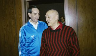 FILE - In this April 1, 1990, file photo, Duke University head coach Mike Krzyzewksi and UNLV head coach Jerry Tarkanian meet in passing between press conferences for the NCAA Championship game in Denver. A year later, UNLV, led by Tarkanian, arrived in Indianapolis needing two wins to become the first undefeated national champion since Indiana in 1976. Kentucky faces Wisconsin Saturday, April 4, 2015, in the national semifinals in Indianapolis. That was the round in which UNLV's undefeated dreams were dashed by Duke. (AP Photo/Ed Reinke, File)