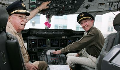 Original Operation Babylift pilots Bill Keating, right, and Ken Healy pose in the cockpit of the World Airways aircraft as it prepares to leave Taipei, Taiwan for Ho Chi Minh City in Vietnam, Wednesday, June 15, 2005.  Mr. Keating and Mr. Healy were part of the group returning to Vietnam for the 30th anniversary of the airlift with a group of more than 20 former orphans. (AP Photo/Ric Feld)
