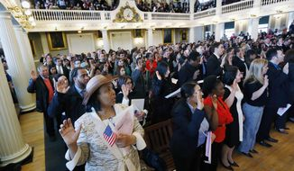 Gina Dominique, lower left, who came from Haiti, takes the oath of U.S. citizenship during a naturalization ceremony in Boston, Thursday, April 2, 2015. Nearly 400 people from dozens of countries ranging from Albania to Zimbabwe took part in the ceremony. (AP Photo/Michael Dwyer)