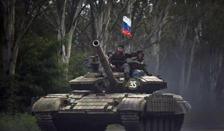In this Sunday, July  29, 2015, file photo, pro-Russian rebels ride on a tank flying Russia's flag on a road east of Donetsk, eastern Ukraine. (AP Photo/Vadim Ghirda, File)