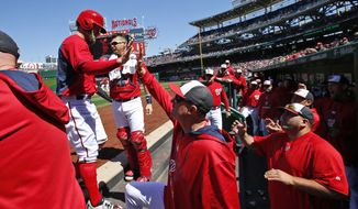 Washington Nationals' Bryce Harper, left, celebrates scoring during the first inning of an exhibition baseball game against the New York Yankees at Nationals Park, Saturday, April 4, 2015, in Washington. (AP Photo/Alex Brandon)