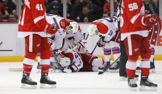 Washington Capitals' Tom Wilson (43) lies on the ice being checked by teammates after being hit by a puck against the Detroit Red Wings in the third period of an NHL hockey game in Detroit Sunday, April 5, 2015. Washington won 2-1. (AP Photo/Paul Sancya)