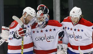 Washington Capitals goalie Braden Holtby, center, celebrates with Karl Alzner, left, and John Carlson, right, after defeating the Detroit Red Wings 2-1 in an NHL hockey game in Detroit, Sunday, April 5, 2015.  (AP Photo/Paul Sancya)