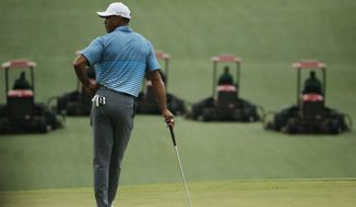 Tiger Woods watches as course workers mow the seventh fairway during a practice round for the Masters golf tournament Monday, April 6, 2015, in Augusta, Ga. (AP Photo/Chris Carlson)
