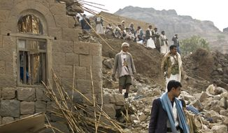 Yemenis stand amid the rubble of houses destroyed by Saudi-led airstrikes in a village near Sanaa, Yemen, in this Saturday, April 4, 2015, file photo. (AP Photo/Hani Mohammed, File)