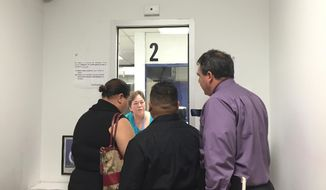 Carolyn Garrido, supervisor at the Office of Vital Statistics at the Guam Department of Public Health and Social Services refuses to accept the marriage license application of Loretta M. Pangelinan, left, and Kathleen M. Aguero, middle on Wednesday, April 8, 2015. The couple's attorney, R. Todd Thompson looks on. Under Guam law, a marriage license is only issued to a couple of the opposite sex, he said. R. Todd Thompson, an attorney for Pangelinan and Aguero, said the couple plans to take their case to federal court. (AP Photo/Grace Garces Bordallo)