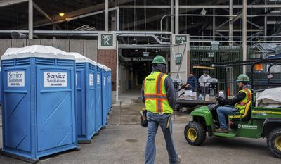 Portable toilets are seen being delivered to Wrigley Field in Chicago, Tuesday, April 7, 2015, before a Chicago Cubs game against the St. Louis Cardinals. (AP Photo/Chicago Tribune, Zbigniew Bzdak)