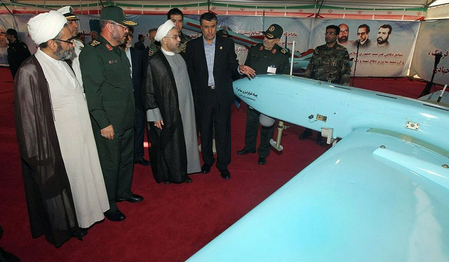"Iran's President Hassan Rouhani (third from left), accompanied by Defense Minister Hossein Dehghan (second from left) looks at a ""Mohajer-4"" Iran-made drone while visiting a defense industry display in Tehran. (Associated Press)"