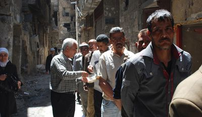 FILE - In this April 24, 2014, file photo provided by the United Nations Relief and Works Agency for Palestine Refugees in the Near East (UNRWA), residents of the besieged Palestinian camp of Yarmouk stand in line to receive aid food distributed by UNRWA on the southern edge of the Syrian capital, Damascus. Conditions in the camp have deteriorated since Islamic State militants muscled their way into it in early April 2015. The militants are trying to consolidate their hold on the camp. (AP Photo/UNRWA, File)