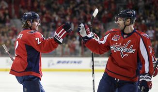 Washington Capitals defenseman Matt Niskanen (2) celebrates his goal with Troy Brouwer (20) during the first period of an NHL hockey game against the Boston Bruins, Wednesday, April 8, 2015, in Washington. (AP Photo/Nick Wass)