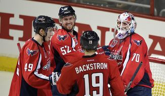 Washington Capitals goalie Braden Holtby (70) celebrates the team's 3-0 win over the Boston Bruins with Mike Green (52), Nicklas Backstrom (19), of Sweden, and Stanislav Galiev (49), of Russia, after an NHL hockey game, Wednesday, April 8, 2015, in Washington. (AP Photo/Nick Wass)