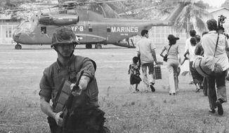 In this April 12, 1975 file photo, U.S. Marines provide cover during Operation Eagle Pull as Americans and Cambodians board Marine helicopters in Phnom Penh during the final U.S. pullout of Cambodia. Five days after Operation Eagle Pull, the dramatic evacuation of Americans, the U.S.-backed government fell as communist Khmer Rouge guerrillas stormed into Phnom Penh. Nearly 2 million Cambodians - one in every four - would die from executions, starvation and hideous torture. (AP Photo/File)