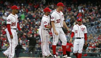 Washington Nationals shortstop Ian Desmond (20), second baseman Dan Uggla (26), and first baseman Ryan Zimmerman (11) come to the mound as starting pitcher Stephen Strasburg (37) is releived during the sixth inning of a baseball game against the New York Mets at Nationals Park, Thursday, April 9, 2015, in Washington. (AP Photo/Alex Brandon)
