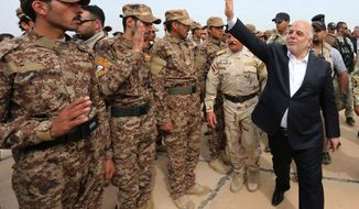 In this photo taken on Wednesday, April 8, 2015 Iraqi Prime Minister Haider al-Abadi, right, salutes security forces and Sunni volunteers at a camp in Habaniyah, 80 kilometers (50 miles) west of Baghdad, Iraq. After victory against Islamic State militants in the city of Tikrit,  Iraq's  prime minister vowed, earlier in the week, to protect the people living in territories controlled by the Islamic State group from any retribution or rights violations when their lands are retaken by government forces. (AP Photo)