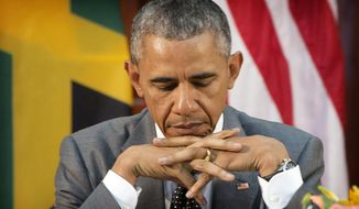 President Barack Obama looks down at his notes during a bilateral meeting with Jamaican Prime Minister Portia Simpson-Miller at the Jamaica House, Thursday, April 9, 2015, in Kingston, Jamaica. (AP Photo/Pablo Martinez Monsivais)