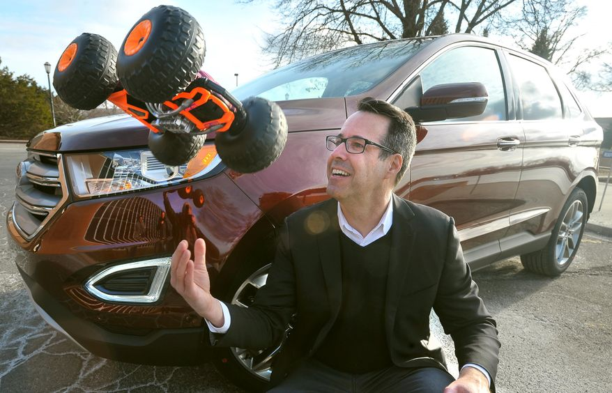 Ford car designer Kevin George tosses the Ricochet, a flipping, double sided R/C toy outside the Ford campus in Dearborn, Mich.