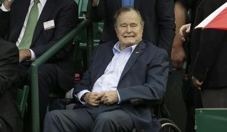 Former President George H.W. Bush, seated, arrives at the River Oaks Country Club just before the quarterfinal match between Jeremy Chardy of France and Kevin Anderson from South Africa was suspended by rain at the U.S. Men's Clay Court Championship Friday, April 10, 2015, in Houston. (AP Photo/Pat Sullivan)