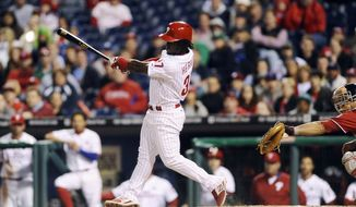 Philadelphia Phillies' Odubel Herrera follows through on a double to right field in the 10th inning of a baseball game against the Washington Nationals, Saturday, April 11, 2015, in Philadelphia. The Phillies won 3-2. (AP Photo/Michael Perez)