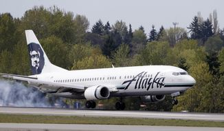 An Alaska Airline jet lands at Seattle-Tacoma International Airport Tuesday, April 23, 2013, in Seattle. (AP Photo/Elaine Thompson)