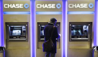 A customer uses an ATM at a branch of Chase Bank in New York in this Jan. 14, 2015, file photo. JPMorgan reports quarterly financial results on Tuesday, April 14, 2015. (AP Photo/Mark Lennihan)