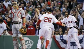 Boston Red Sox's Mike Napoli, behind left, and Dustin Pedroia, right, greet Red Sox's Brock Holt (26) at the plate as he scores on a double by Mookie Betts in the second inning of a baseball game at Fenway Park in Boston, Tuesday, April 14, 2015. Washington Nationals catcher Wilson Ramos stands at left.  (AP Photo/Elise Amendola)
