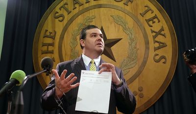 Rep. Larry Phillips, Sherman Republican, holds up the change position report with the errors used as a point of order to try to delay an open carry bill on the House floor Tuesday in Austin, Texas. (Associated Press)