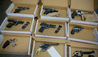 Firearms evidence is on display during a news conference in Portland, Ore., on Dec. 9, 2013. Oregon senators have approved a bill requiring background checks on most private gun sales. (Jamie Francis/The Oregonian via AP) **FILE**