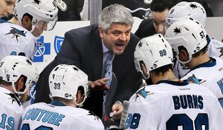FILE - In this March 29, 2015, file photo, San Jose Sharks head coach Todd McLellan, center, talks to his team during a timeout in the third period of an NHL hockey game against the Pittsburgh Penguins in Pittsburgh. McLellan has been picked as head coach for Canada's national team at the upcoming World Championship, Hockey Canada announced Tuesday, April 14, 2015. The tournament runs from May 1-17 in the Czech Republic.  (AP Photo/Gene J. Puskar, File)