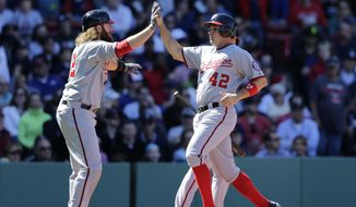 Washington Nationals' Ryan Zimmerman, right, is congratulated by teammate Jayson Werth after they both scored on a three-run double by Wilson Ramos against the Boston Red Sox during the third inning of a baseball game at Fenway Park in Boston, Wednesday, April 15, 2015. (AP Photo/Charles Krupa)
