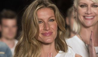 Brazilian supermodel Gisele Bundchen smiles and gestures at the end of the show from the Colcci Summer collection at Sao Paulo Fashion Week in Sao Paulo, Brazil, Wednesday, April 15, 2015. Bundchen, the Brazilian supermodel who has lit up catwalks around the world for 20 years, is retiring from the runway. (AP Photo/Andre Penner)