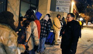 FILE - In this Dec. 5, 2013 file photo, Tom Tuning, right, greets homeless men who wait for the opening of the St. Francis Center's day shelter, where Tuning works, in downtown Denver. Homeless people in Colorado would have a right to seek civil remedies if they're harassed by authorities while resting in public with a bill getting its first hearing at the state Legislature Wednesday, April 15, 2015. (AP Photo/Brennan Linsley, file)