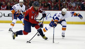 Washington Capitals left wing Alex Ovechkin (8), from Russia, shoots past New York Islanders defenseman Brian Strait (37) during the first period of Game 1 of a first-round NHL hockey Stanley Cup playoffs series, Wednesday, April 15, 2015, in Washington. (AP Photo/Alex Brandon)