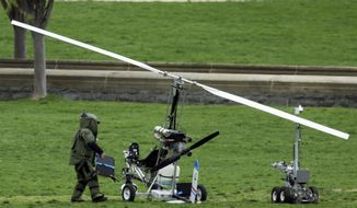 A member of a bomb squad checks a small helicopter after a man landed on the West Lawn of the Capitol in Washington, Wednesday, April 15, 2015. (AP Photo/Manuel Balce Ceneta)