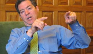 In this April 13, 2015 photo, Kansas Republican Gov. Sam Brownback makes a point during an interview in his office in the Statehouse in Topeka, Kan. Brownback is preparing to sign welfare legislation restricting how poor families can spend cash assistance from the state. The Republican governor scheduled a Thursday, April 16, 2015, morning signing ceremony at the Statehouse. (AP Photo/John Hanna)