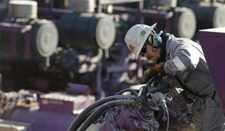 FILE - In this March 25, 2014 file photo, a worker oils a pump during a hydraulic fracturing operation at a gas and oil well pad near Mead, Colo. The University of Colorado's governing Board of Regents could vote Thursday April 16, 2015 on whether to stop investing in coal, oil and gas. The regents are expected to discuss a proposal from a student-led group called Fossil Free CU. (AP Photo/Brennan Linsley, file)