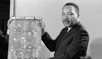 In this March 1968 file photo, Martin Luther King Jr. displays the poster for his planned Poor People's Campaign. Assassinated on April 4 1968, the civil rights leader did not live to see the campaign come to fruition. (AP Photo/Horace Cort) ** FILE **