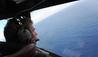 In this April 13, 2014, file photo taken from the Royal New Zealand Air Force (RNZAF) P-3K2-Orion aircraft, co-pilot Squadron Leader Brett McKenzie looks out of a window while searching for debris from missing Malaysia Airlines Flight 370, in the Indian Ocean off the coast of western Australia. (Greg Wood/Pool Photo via AP)