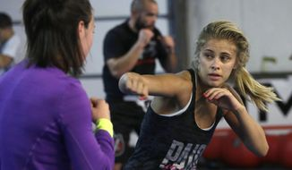 In this Monday, April 13, 2015, photo, mixed martial arts fighter Paige VanZant, right, spars with Sarah Jamila at Ultimate Fitness in Sacramento, Calif. VanZant, 21, is scheduled to fight Felice Herrig in an Ultimate Fighting Championship strawweight match in New Jersey on Saturday. (AP Photo/Rich Pedroncelli)