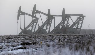 FILE - In this Dec. 19, 2014 file photo, oil pump jacks work in unison on a foggy morning in Williston, N.D. The North Dakota Legislature is looking at restructuring oil taxes as a hedge against falling crude prices. Oil companies could see a big tax cut if crude prices continue to slide, and the state could lose billions of dollars. (AP Photo/Eric Gay, File)