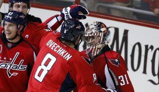 Washington Capitals left wing Alex Ovechkin (8), from Russia, embraces goalie Philipp Grubauer (31) after Game 2 against the New York Islanders in an NHL hockey first-round  playoff series Friday, April 17, 2015, in Washington. The Capitals won 4-3. (AP Photo/Alex Brandon)