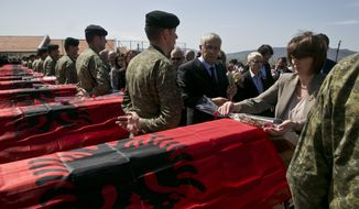 Kosovo President Atifete Jahjaga lays flowers on coffins of 21 Kosovo Albanians killed during 1998-99 war with Serbia as they are buried in the village of Cikatove e Vjeter, Kosovo, on Friday, April 17, 2015. (AP Photo/Visar Kryeziu)