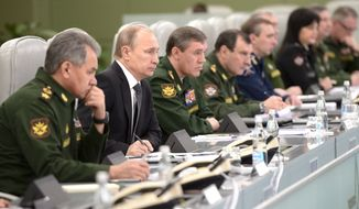 Russian President Vladimir Putin, second left, flanked by Defense Minister Sergei Shoigu, left, and Chief of the General Staff of the Russian Armed Forces Valery Gerasimov, third left, visits the National Defense Control Center in Moscow, Russia, Friday, April 17, 2015. (Alexei Nikolsky/ RIA-Novosti, Kremlin Pool Photo via AP)