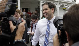 Republican presidential candidate, Sen. Marco Rubio, R-Fla., laughs as he is surrounded by media at a campaign house party in Manchester, N.H., in this April 17, 2015, file photo. (AP Photo/Elise Amendola)
