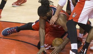 Washington Wizards' Nene Hilario gathers up a loose ball against the Tornto Raptos during the first half in Game 1 of the NBA basketball playoffs in Toronto, Saturday, April 18, 2015. (Chris Young/The Canadian Press via AP)   MANDATORY CREDIT