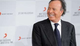 FILE - In this May 12, 2014 file photo, Latin pop icon Julio Iglesias poses for photographers at a news conference where he was named the 'Most Successful Latin Artist of All Time',  at a central London venue. Iglesias and three other prominent music industry figures will receive honorary degrees from Boston's Berklee College of Music at its commencement next month. (Photo by Jonathan Short/Invision/AP, File)