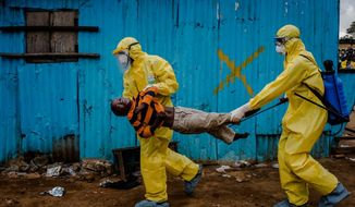 This Sept. 5, 2014, photo by New York Times photographer Daniel Berehulak, part of a winning series,  shows James Dorbor, 8, suspected of being infected with Ebola, being carried by medical staff to an Ebola treatment center in Monrovia, Liberia. The boy, who was brought in by his father, lay outside the center for at least six hours before being seen.  Berehulak is the winner of the 2015 Pulitzer Prize for Feature Photography, announced Monday, April 20, 2015, at Columbia University in New York. (Daniel Berehulak, New York Times, Columbia University via AP)
