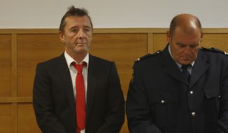 AC/DC drummer Phil Rudd, left, stands in the dock at a court in Tauranga, New Zealand on Tuesday. Rudd pleaded guilty to a charge of threatening to kill a man who used to work for him. He also pleaded guilty to possessing methamphetamine and marijuana. (Associated Press)