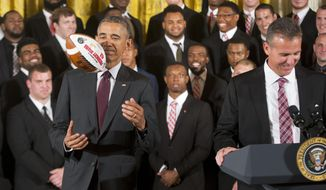President Barack Obama tosses a football presented to him by Ohio State football coach Urban Meyer, right, as he welcomed the NCAA College Football Playoff National Champion Ohio State Buckeyes, Monday, April 20, 2015, during a ceremony in the East Room of the White House in Washington. (AP Photo/Pablo Martinez Monsivais)