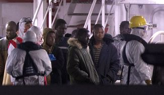 Survivors of the boat that overturned off the coasts of Libya Saturday, wait to disembark from Italian Coast Guard ship Bruno Gregoretti, at Catania Harbor, Italy, Monday, April 20, 2015. A smuggler's boat crammed with hundreds of people overturned off Libya's coast as rescuers approached, causing what could be the Mediterranean's deadliest known migrant tragedy and intensifying pressure on the European Union Sunday to finally meet demands for decisive action. (AP Photo/Alessandra Tarantino)