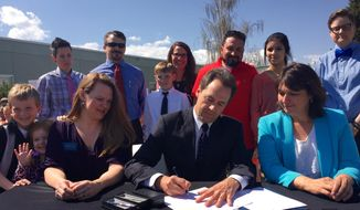 Montana Gov. Steve Bullock signs the Bully Free Montana Act Tuesday, April 21, 2015, at Jefferson Elementary in Helena, Mont., while bill sponsor Rep. Kim Dudik, left, and Superintendent of Public Instruction Denise Juneau look on. (AP Photo/Lisa Baumann)